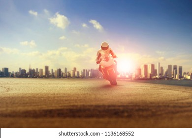 man riding big motorcycle on sharp curve against city building scene