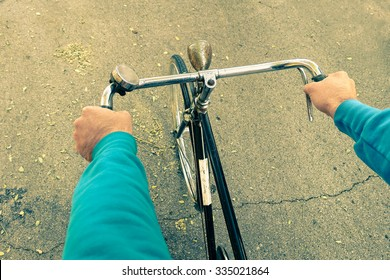 Man riding bike - Male hands on vintage bicycle on the road - Cyclist guy on alternative transportation - Student arms on retro vehicle - Green concept of environment preservation and  energy saving