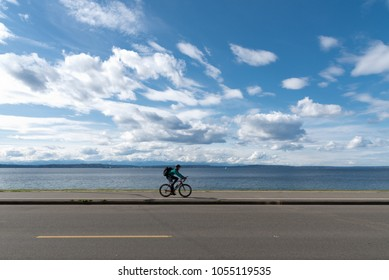Man riding bike near shore on West Seattle beach under afternoon partly cloudy blue sky seascape.