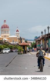 Man riding bike on street in city Granada, Nicaragua, Central America