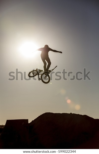 Man riding a bmx bike performing a trick against sunset sky. Fall down. Extreme sport