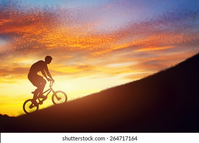 Man riding a bmx bike uphill against sunset sky. Active lifestyle, motivation, strength, challenge