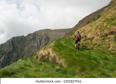 man riding with an electric bicycle (e-bike, ebike, mtb) valley, mountain, summer, sport, adventure, alps, Mount Legnone, Como Lake, Italy