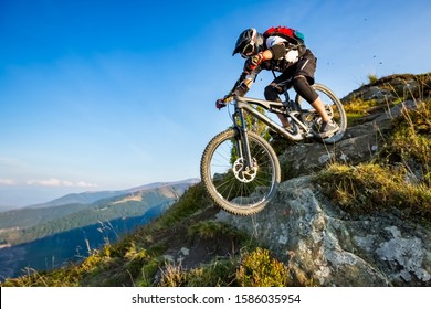 A man is riding enduro bicycle, on the rock trail. Background of mountains and blue sky. Beautiful summer day. Mountain bike race.