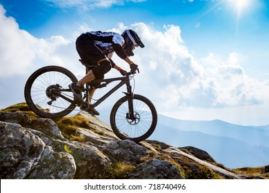 A man is riding enduro bicycle, on the background of mountains and blue sky. Beautiful summer day.