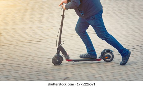 Man riding fast on kick scooter on pavement in the city. Rider pushing off ground and moving down the street, side view. Push off on scooter. Healthy lifestyle, transportation concept