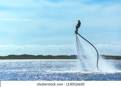 a man is riding a flyboard on a lake on a sunny day, toned
