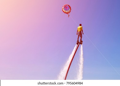 man is riding a flyboard on the sea beach with blue sky and parachute on the background