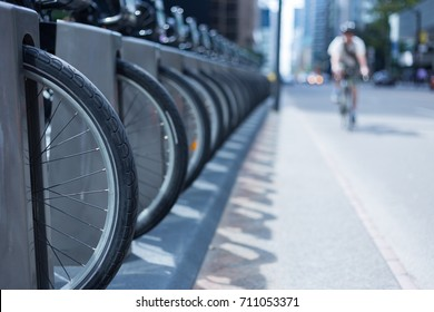 man riding his bike on a busy city street with cars and skyscrapers in the background and a row of wheel and bike at a bike rental station