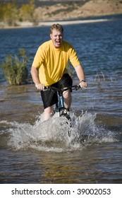 A man riding his bike through the water.