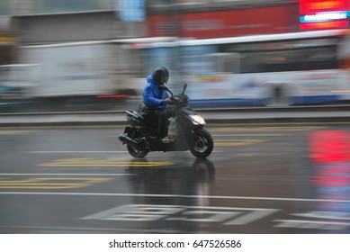 A man riding his scooter in the rain, a lifestyle of people living in urban area, Taipei, Taiwan