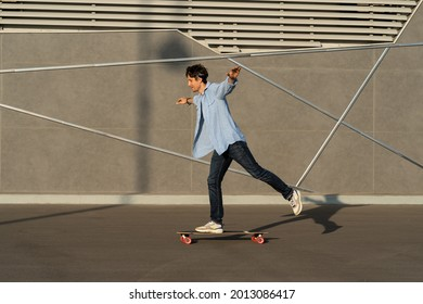 Man riding longboard perform tricks on skateboard in urban street skatepark. Casual hipster guy wearing jeans shirt and bandana skateboarding. Leisure activity, sport extreme, city lifestyle concept