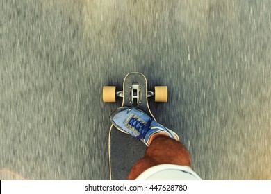 Man riding a longboard, a plan view on the move, close-up, first-person view. Lens, flare effect