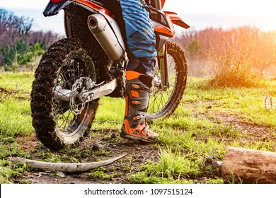 man riding a motocross in a protective suit in the mud