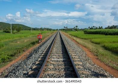 Man riding motorbike parallel to railroad tracks.