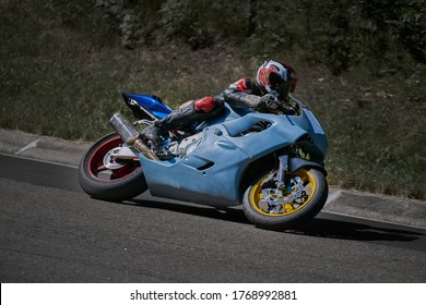 Man riding motorcycle in asphalt road curve with rural,motorcycle practice leaning into a fast corner on track