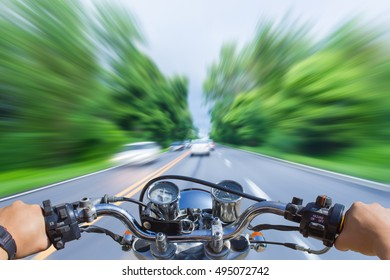 Man riding motorcycle, blur image of motion on the road as background.