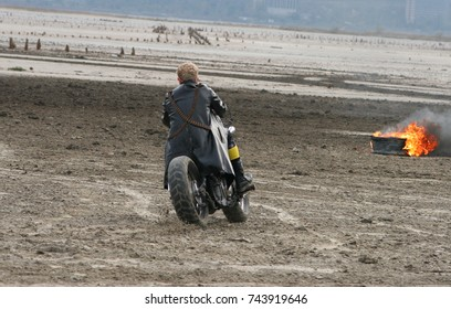 a man is riding a motorcycle near a fire
