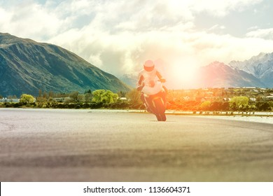 man riding motorcycle on highway against mountain scene