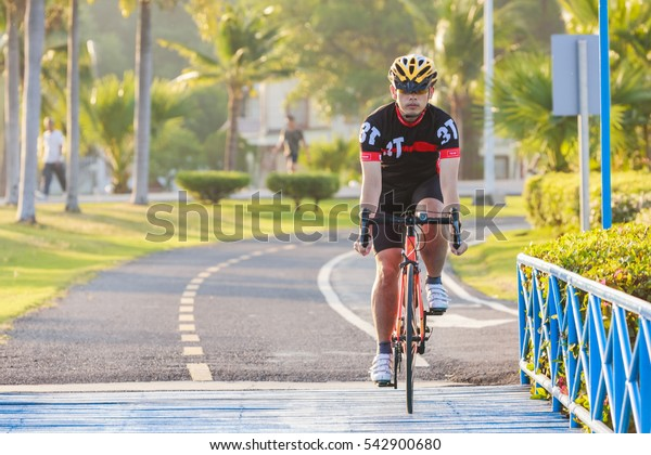 Man riding mountain bike on bridge trail at sunrise at public park.