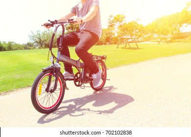 A man riding on electric bicycle in a park
