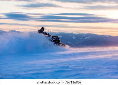 A man is riding snowmobile. Good winter time. Clowdy sky, sunset light.