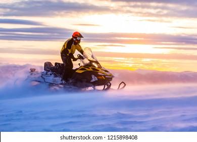 Ein Mann fährt Schneemobil in den Bergen. Schönes Morgenlicht. Blaue Schatten.