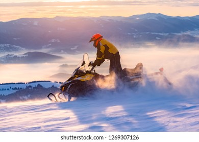 A man is riding snowmobile in mountains. Beautiful morning light. Blue shadows.