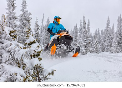 A man is riding snowmobile in mountains. jump on a snow bike. pilot on a sports snowmobile in a mountain forest. The concept of skidooking. rider in a bright suit on a colorful snowy moto. Hi quality