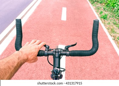 Man riding sport bike top view on handle bar and road perspective - Male hand on bicycle brakes on urban cycle path - Green concept of everyday transport for healthy lifestyle and environment respect