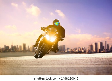 man riding sport motorcycle lean on curve road against urban skyline background