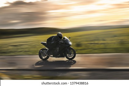 Man riding a sports motorbike at sunset, flying by with a field in the background.