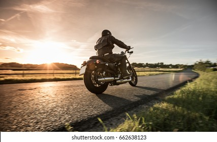 Man riding sportster motorcycle on countryside during sunset.