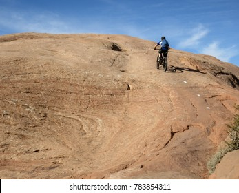 Man riding up a stone hill at Slickrock trail in Moab, Utah