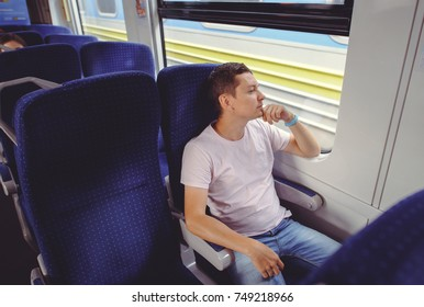 a man is riding a train, traveling by rail.