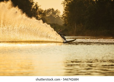 Man riding wakeboard on lake with splashes of water. Man water skiing at sunset.