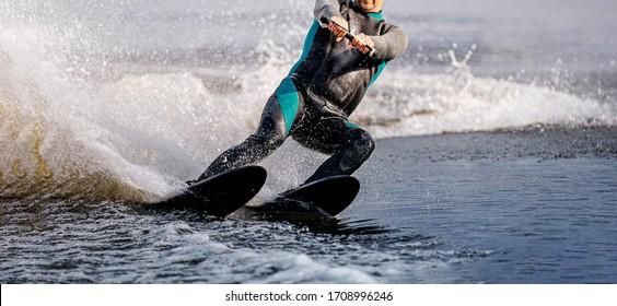 man riding water ski on summer lake. black neoprene wetsuit on full body