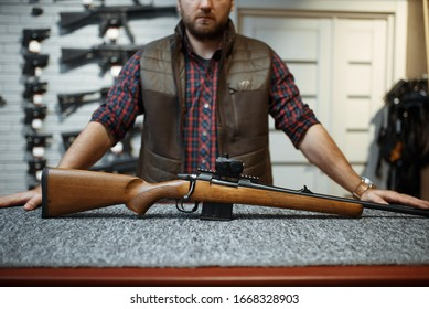 Man with rifle standing at counter in gun shop