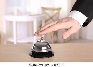 Man ringing service bell in hotel lobby