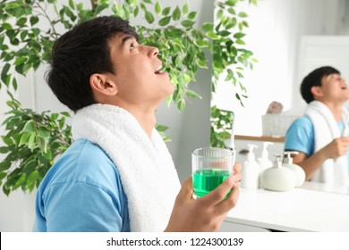 Man rinsing mouth with mouthwash in bathroom. Teeth care