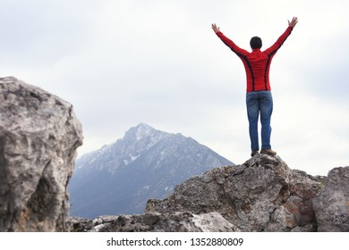 Man rise a hands on top of the mountain. Concept of freedom, man on wild nature in mountains