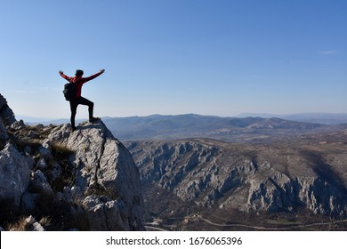 Man rise a hands on top of the mountain. Concept of freedom. Young man enjoy on a cliff edge