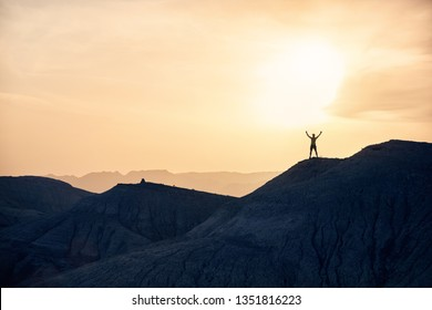 Man with rising hands in silhouette running on the mountains in the desert at sunset