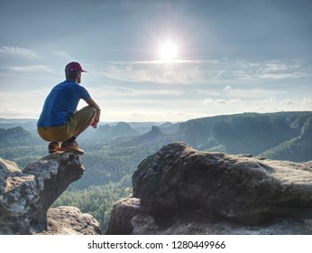 Man risk at the edge. Man in training sports clothes  sit on cliff and enjoying far view. View into misty hilly valley bellow
