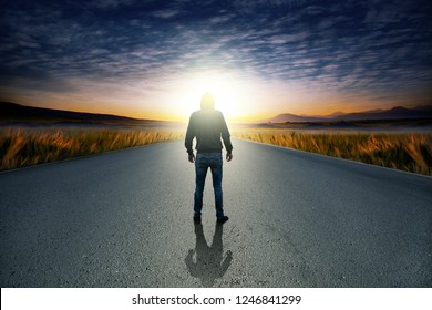 man in  road at sunset