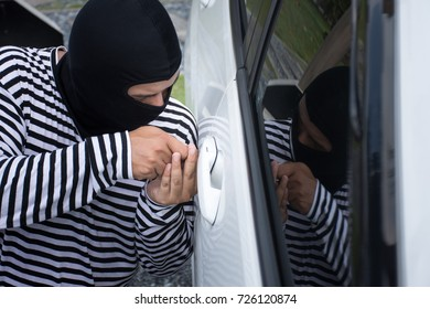 The man robber with a balaclava on his head trying to break into the car. He uses a screwdriver/Selective focus/Criminal and car thief concept