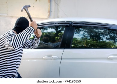 The man robber with a balaclava on his head holding a hammer trying to break into the car/Selective focus/Criminal and car thief concept