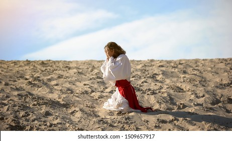 Man in robe repenting for sins, praying to God in desert, pangs of conscience