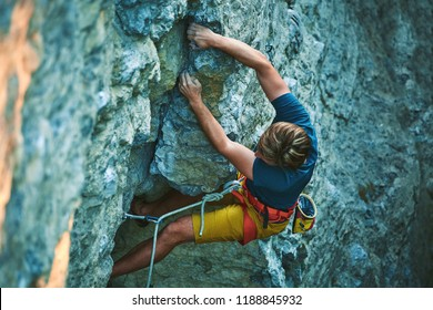 man rock climber in bright yellow shorts climbing the challenging route on the cliff. rock climber climbs on a rocky wall. man making hard move