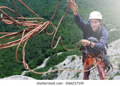 man rock climber climbed on the cliff. man rock climber on the ledge of the cliff and throws a rope to a partner